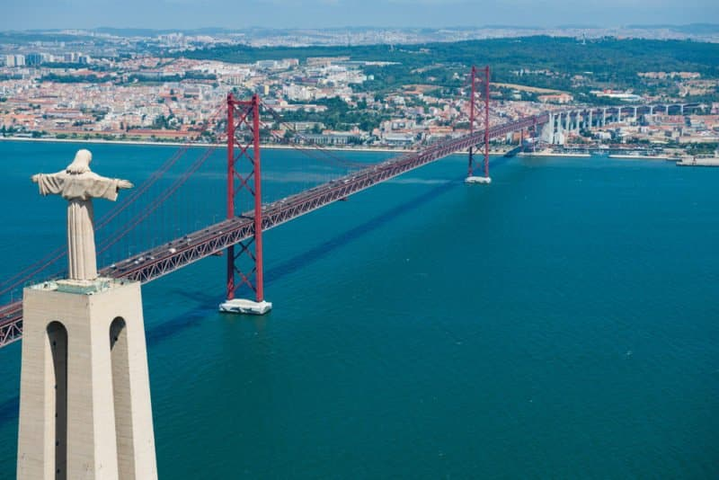 Aerial View of Christ the King Statue and 25th of April Bridge, Lisbon, Portugal. @shutterstock
