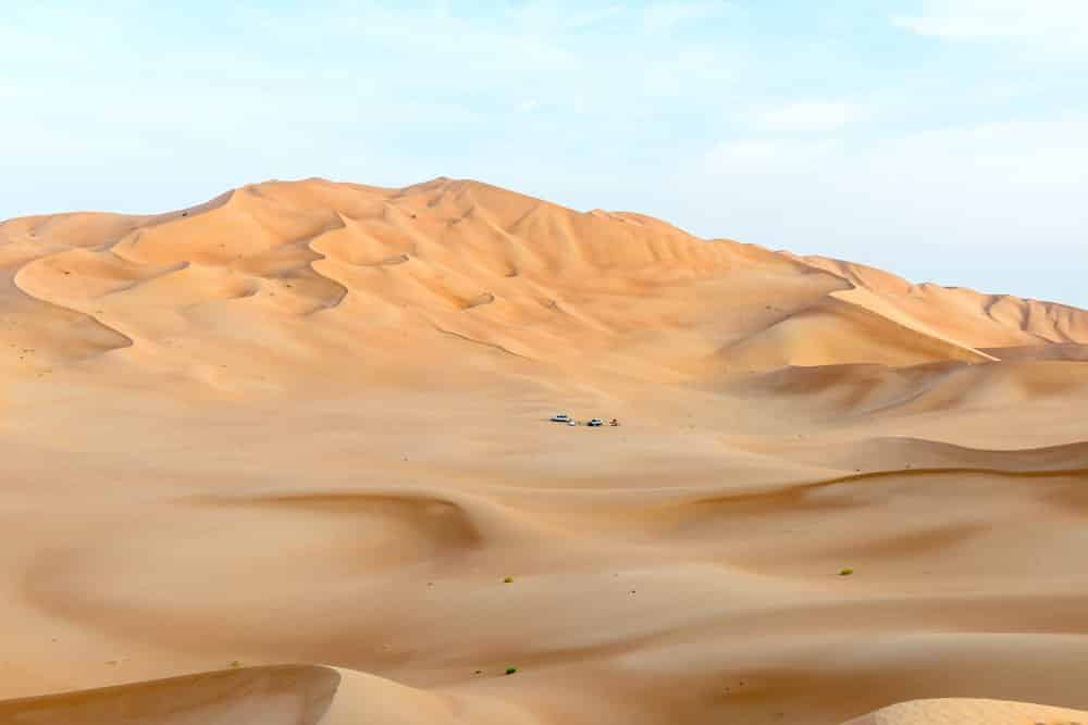 People with tents and cars among dunes in Rub al-Khali desert, Dhofar region (Oman)