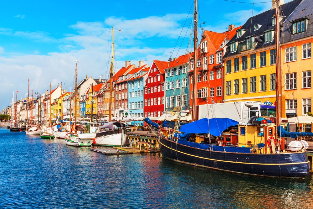 Scenic summer view of Nyhavn pier with color buildings, ships, yachts and other boats in the Old Town of Copenhagen, Denmar