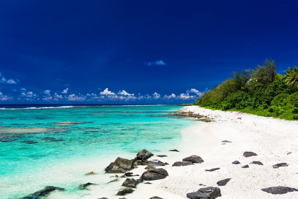 Amazing beach with white sand and black rocks on Rarotonga, Cook Islands
