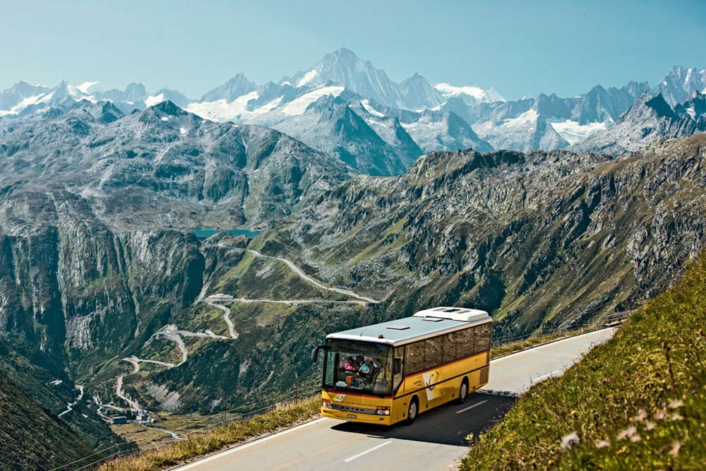Postal bus at the Furkapass in Valais. View of the Grimselpass and the Finsteraarhorn (4274 m) in the distance. Picture Credit: Swiss Travel Pass AG