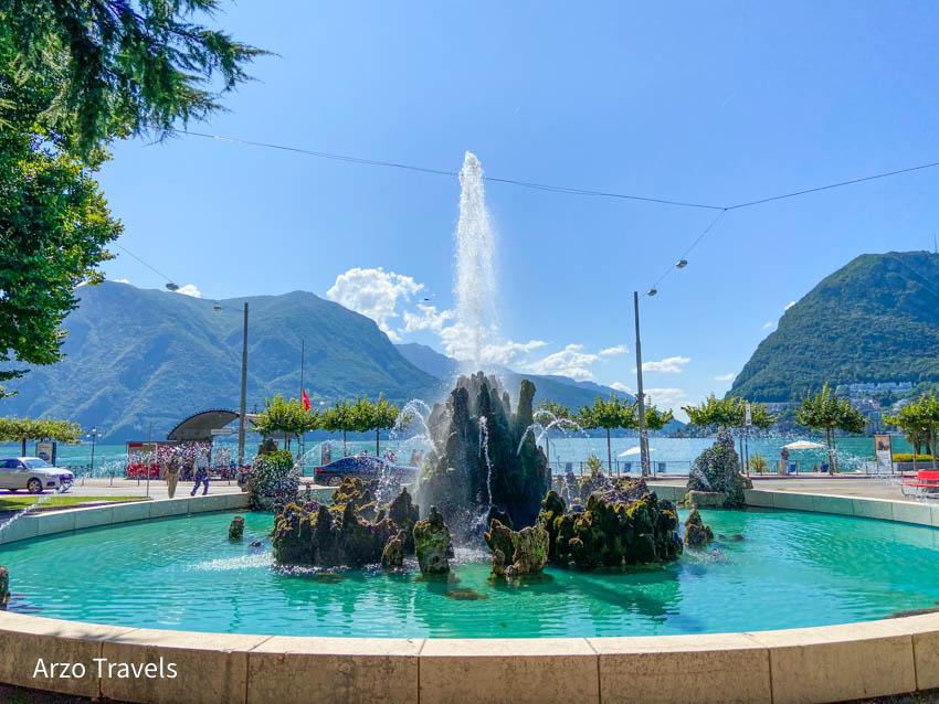 PIAZZA MANZONI with water fountain and Lake Lugano